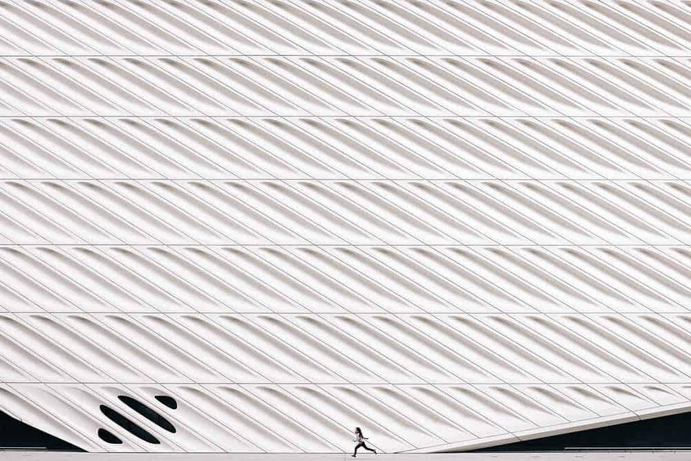 Personnage qui court devant une architecture moderne