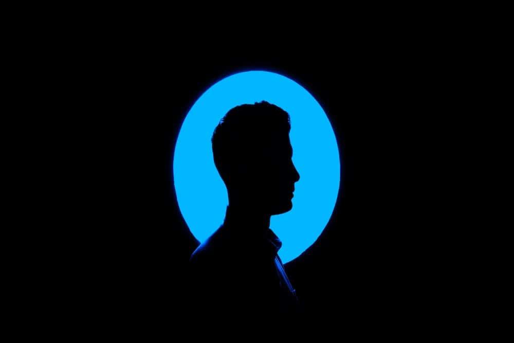 Ombre d'un profil sur fond bleu et environnement noir