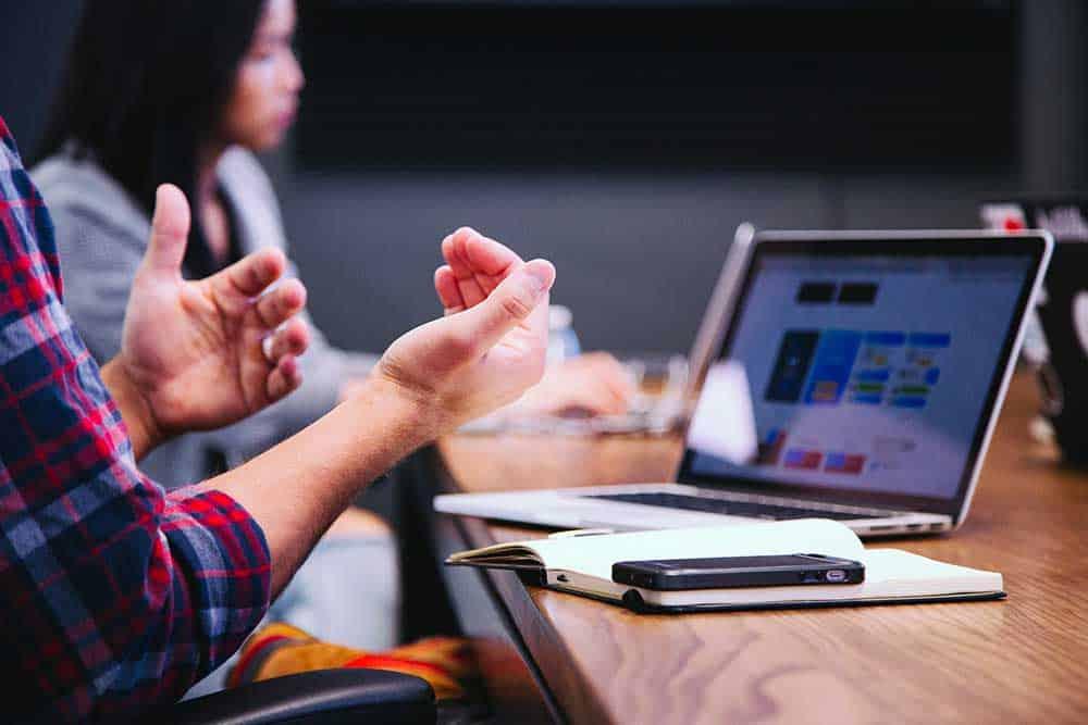 Zoom sur les mains d'un participant à une réunion avec un ordinateur, un cahier et un mobile