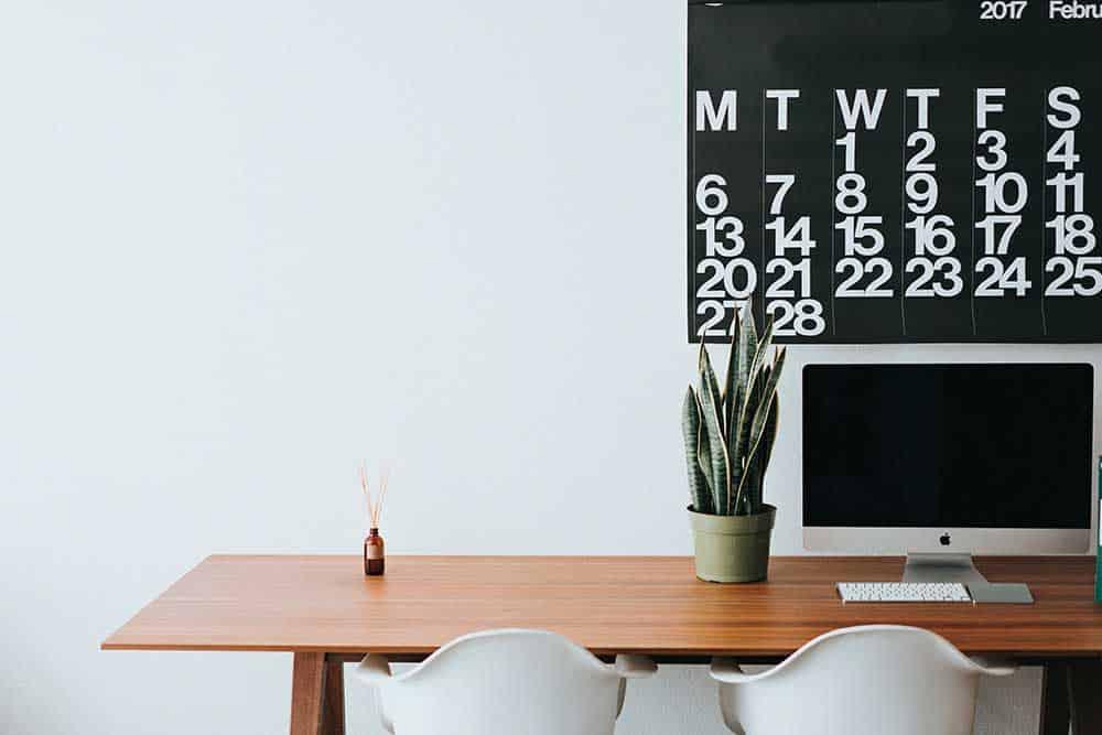 Bureau avec un ordinateur une plante et de l'encens