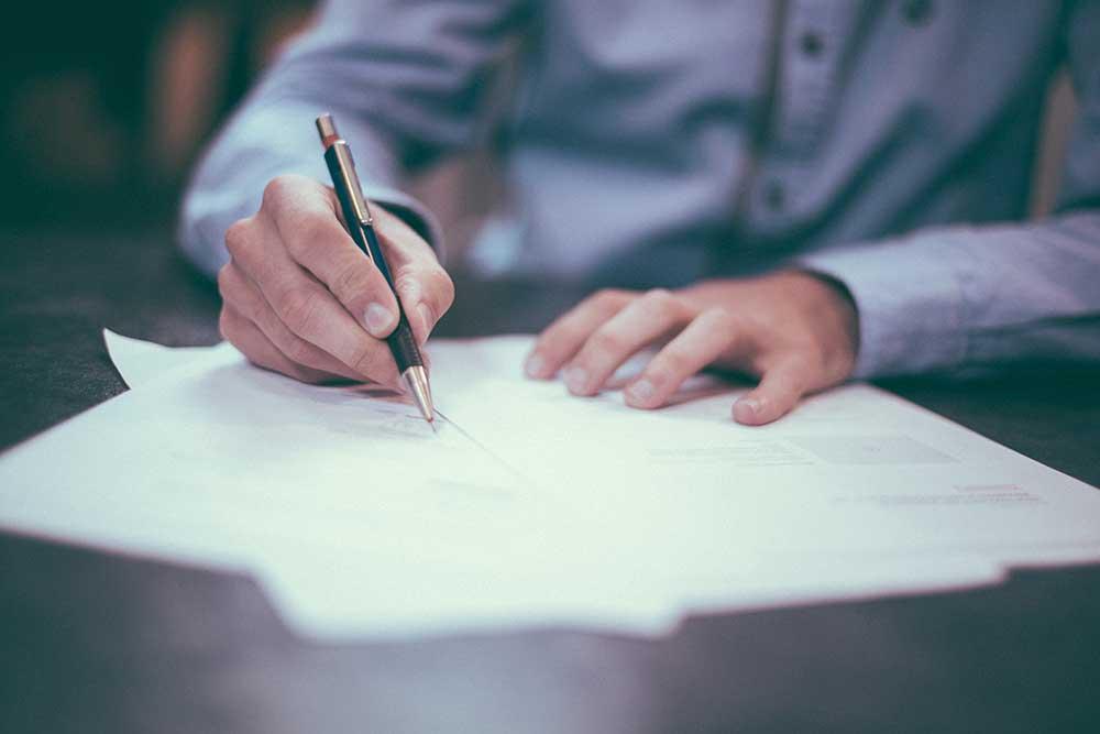 Homme tenant un stylo pret a signer des documents