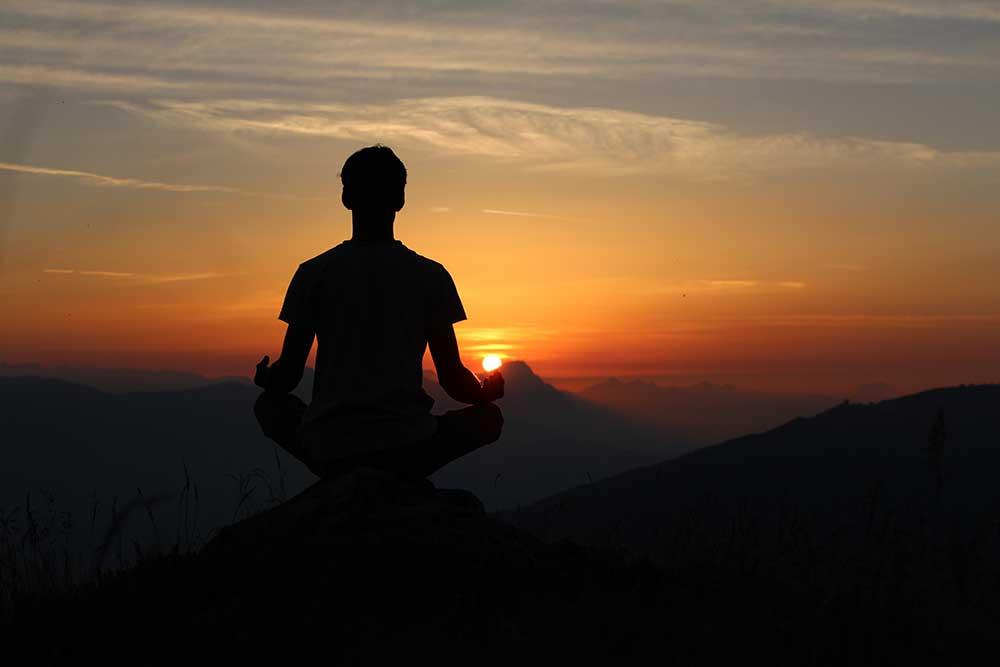 Homme en méditation devant un coucher de soleil