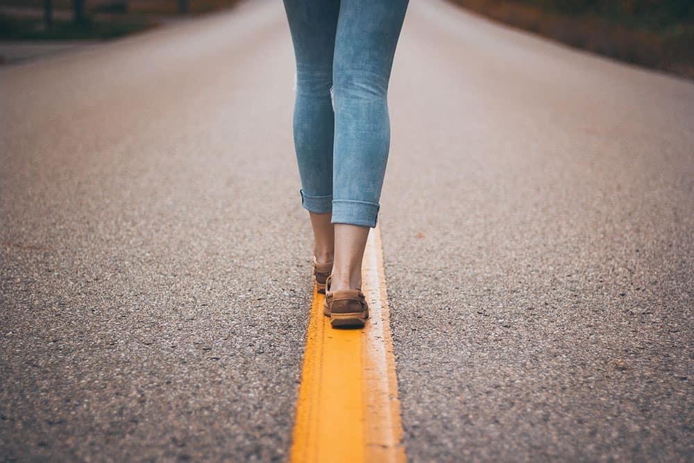 Femme marchant sur une ligne jaune