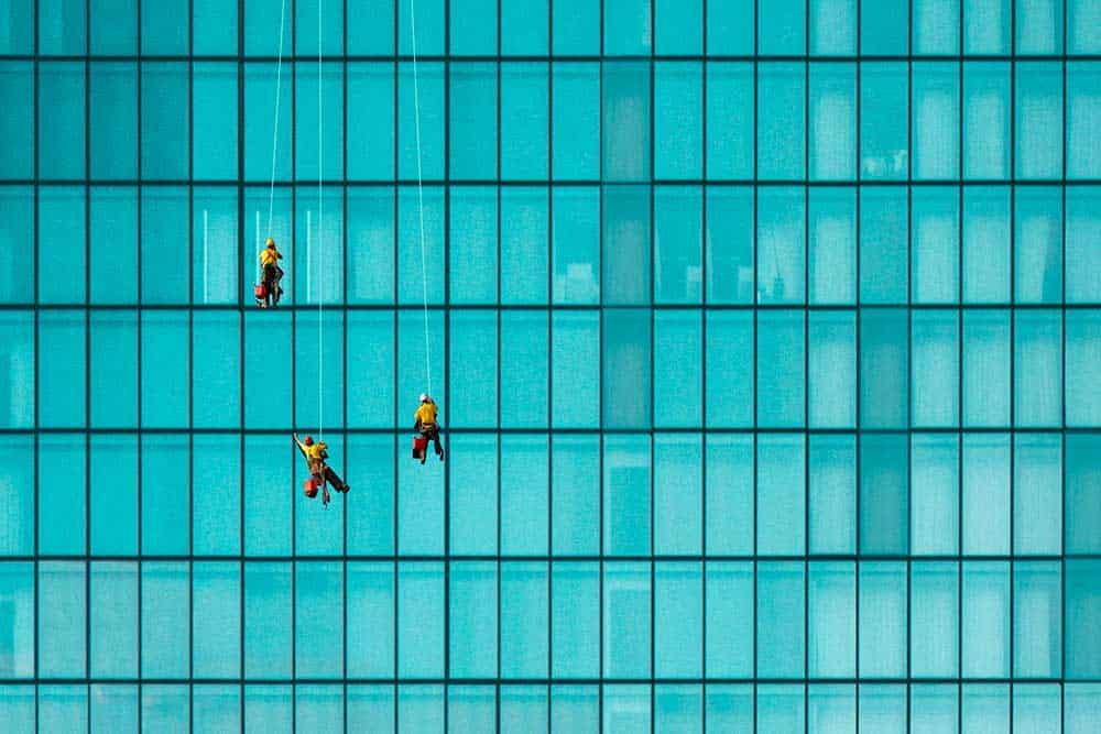 Travailleurs de l'extrême qui nettoient des vitres d'un gratte ciel