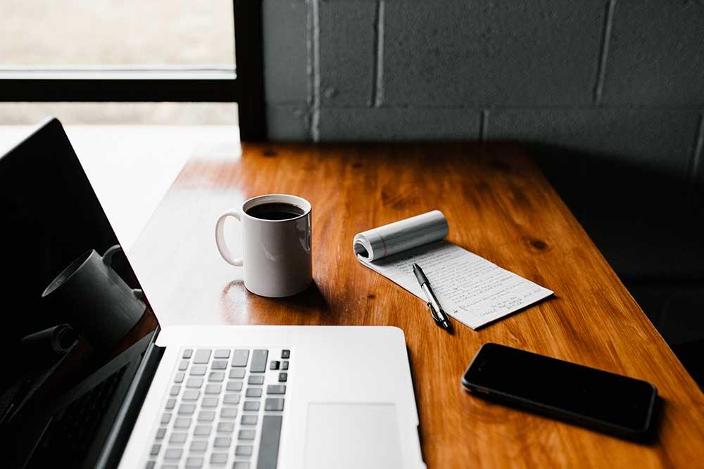 Bureau avec un ordinateur un cafe un mobile et un cahier de note