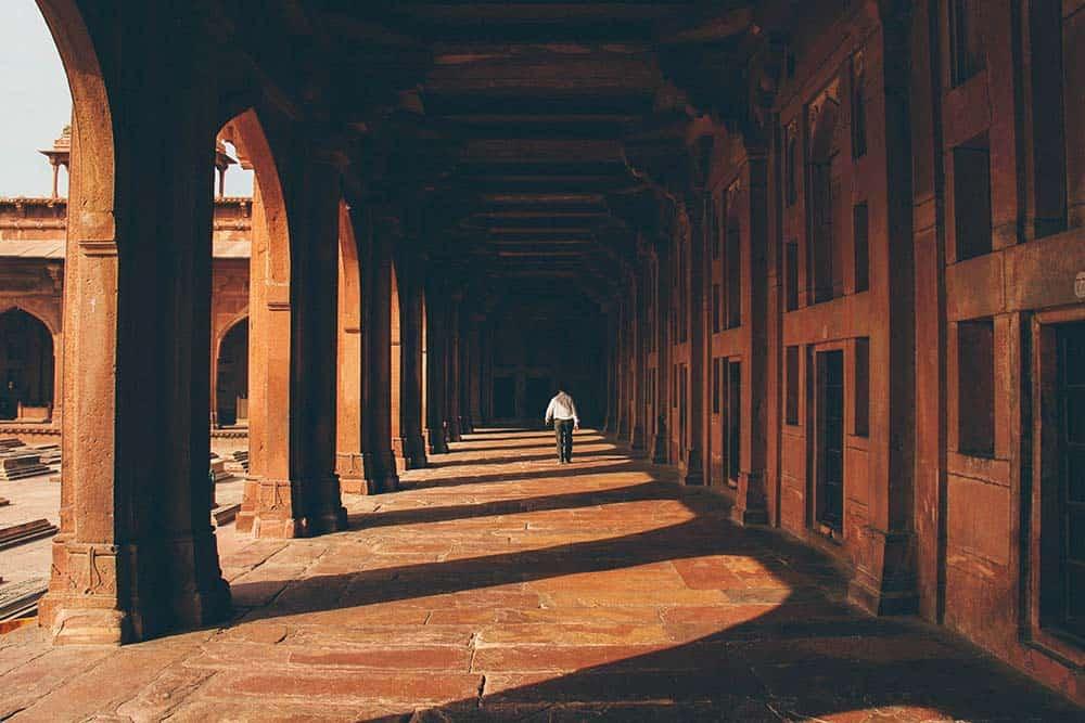 Homme de dos marchant sous les arches d'un bâtiment ancien