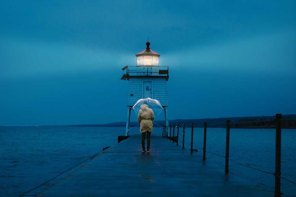 Personne de dos un parapluie transparent au dessus de la tete et qui fait face à un phare au bout d'un ponton